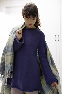 The barely rolled collar at the shallow scoop neckline contributes to the drape and subtle shaping in this stockinette tunic. The diagonal lines of the waist's slight A-line, bell sleeves, and the raglan shoulder create feminine curves in an otherwise masculine garment.