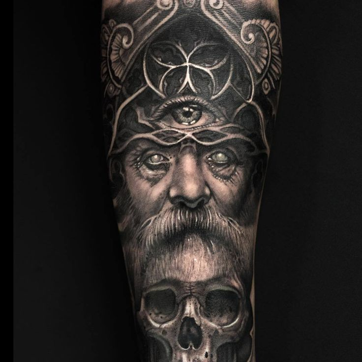 Realistic Viking tattoo of Odin on the arm. With the third eye and a skull ….