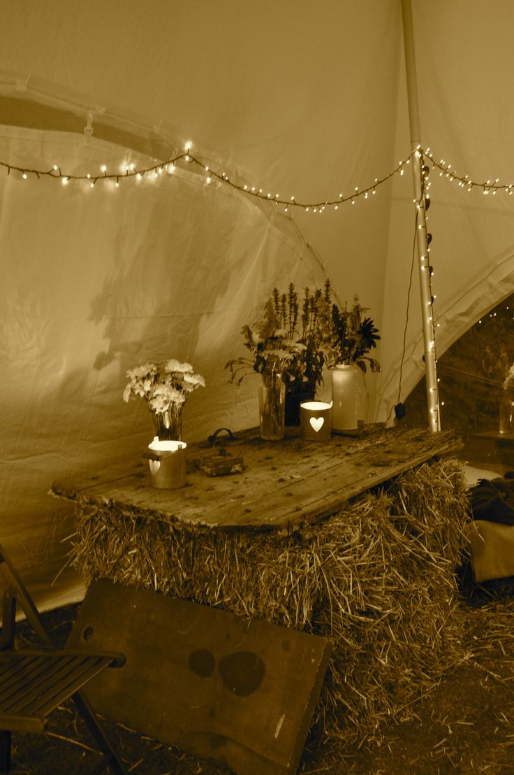 English country summer garden party, straw bales, old wooden door, flowers, fairy lights, makeshift bar