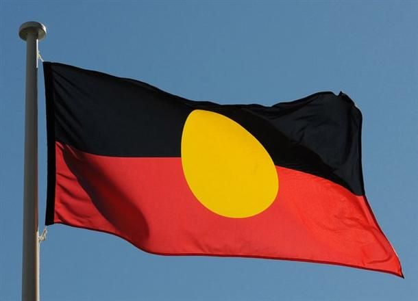 """Australian Aboriginel Flag designed in 1971 by Aboriginal artist Harold Thomas, who holds intellectual property rights in the flag's design, and is descended from the Luritja people of Central Australia /  photo by Bruce Palme. / The Australian Aboriginal Flag is a flag that represents Indigenous Australians. It is one of the official """"Flags of Australia"""", and holds special legal and political status, but it is not the """"Australian National Flag""""."""