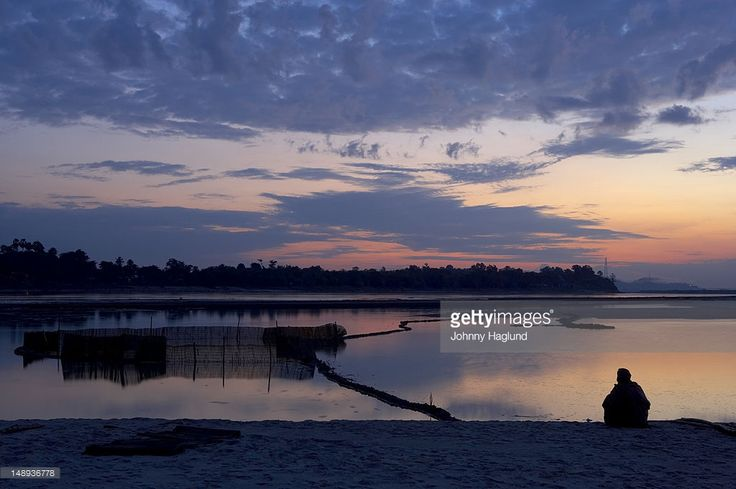 Stock Photo : Sunrise over the Brahmaputra river, with fisherman on the shore waiting for fish to enter his nets.