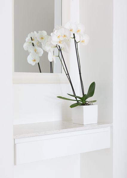 ETEISEN PEILIPÖYTÄ  Töölöläisen kodin eteissyvennykseen asennettiin pieni ja kätevä peilipöytä. Kvartsikomposiittitason alla on valkoinen kiiltävä vedinurallinen laatikko. Tason väri on Aspen ja paksuus 20mm.
