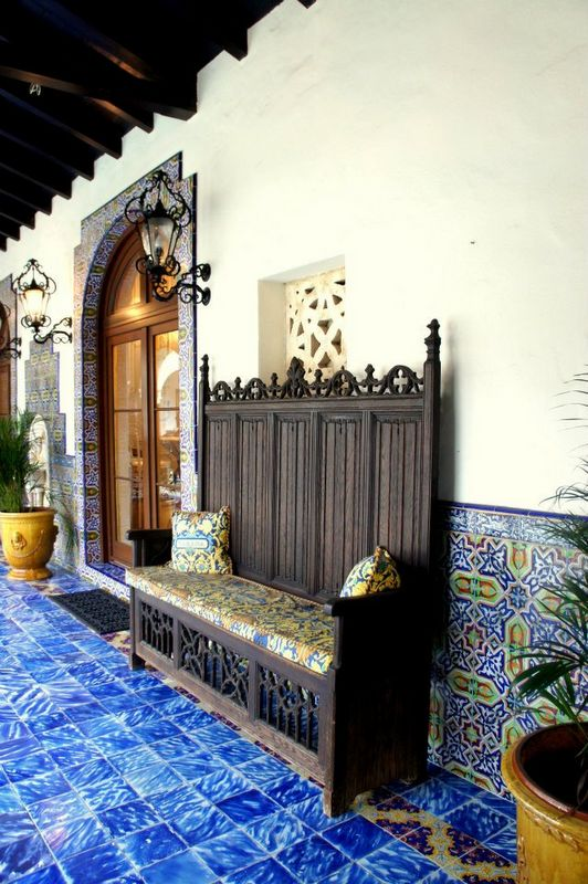 Spanish style very pretty wall tiles and the bright yellow planter is a great contrast accent in there.