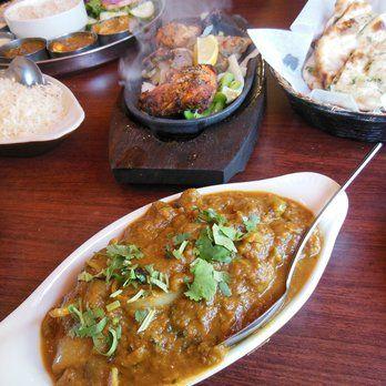 Flavor of India - Clockwise: Tandoori Chicken and Lamb Sheek (Shish) Kabob on sizzling platter, Garlic Naan, Lamb Karahi, and accompanying Basmati Rice - Lincoln City, OR, United States