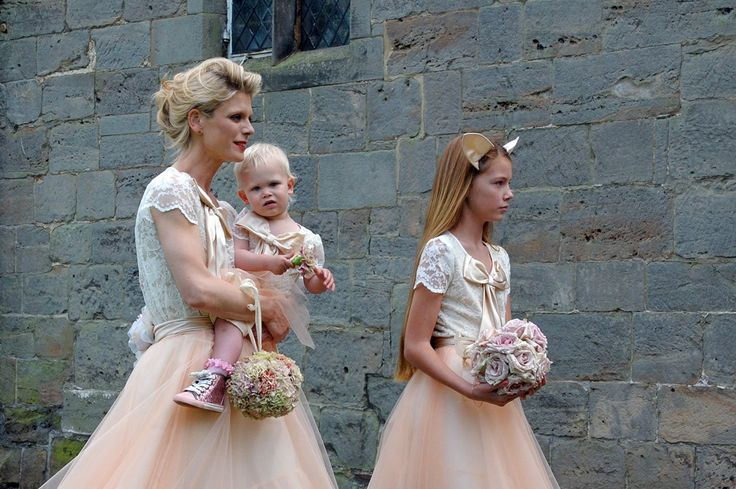 Actress Emilia Fox wearing a peach tulle and lace bodice bridesmaids dress with a bow. Carrying a pomander.  Kate Halfpenny's wedding to James Lee Duffy.  http://www.elegantandwild.co.uk/