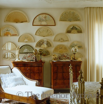 A collection of framed antique fans creates a backdrop for this feminine bedroom