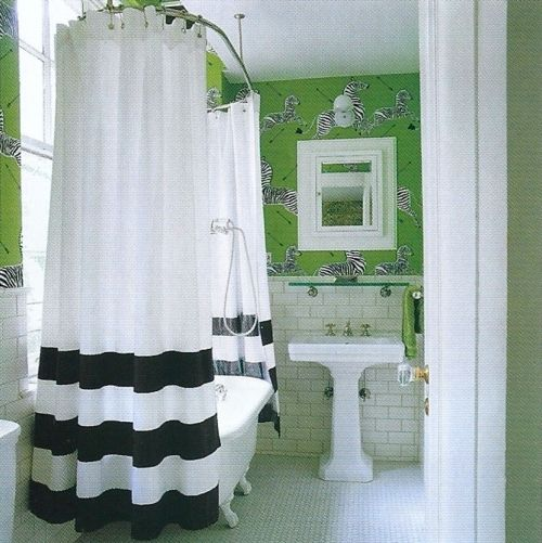 Black and white shower curtain, white subway tile and Scalamandre zebra-patterned wallpaper in a bright green, black and white.