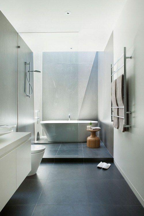 baño moderno, de suelo color carbon, y mampara que separa la zona de baño con ducha y bañera