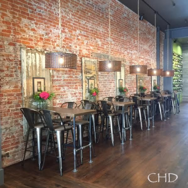 brick wall with reclaimed wood accent panels, tables made from pipe, tolix metal bar stools, rustic drum shade pendant in restaurant wine bar. Note the lime green wall in back next to gray walls.