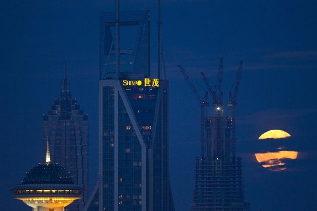 The moon rises over the skyline of Lujiazui financial district of Pudong in Shanghai ~ Blue Moon  8-31-2012