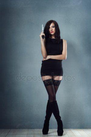 c982dc7442cc831 Скачать - Сексуальная девушка брюнетка в черном платье, сапоги держит  пистолет и оглядываясь назад — стоковое изображение