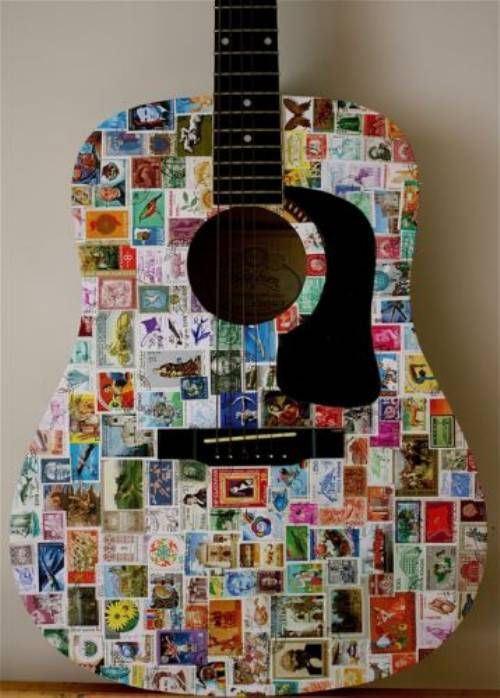 Guitar covered in postage stamps. Must need to go somewhere far away