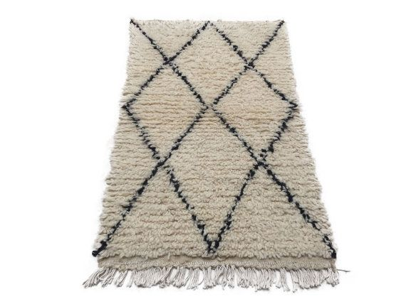 The Berbers are also called Amazigh, or 'free men', and this gorgeous vintage rug in beige and black represents many of the traditions that define the Berber way of life. Hand-woven by the women of the Azilal province in the Atlas Mountains, this plush rug is created with natural lamb wool fibers. Its characteristic diamond-shape design motifs evoke everything from the renewal of the land to the spirituality of man. Place it as a Door mat in your Living room or dining room , front of your TV…