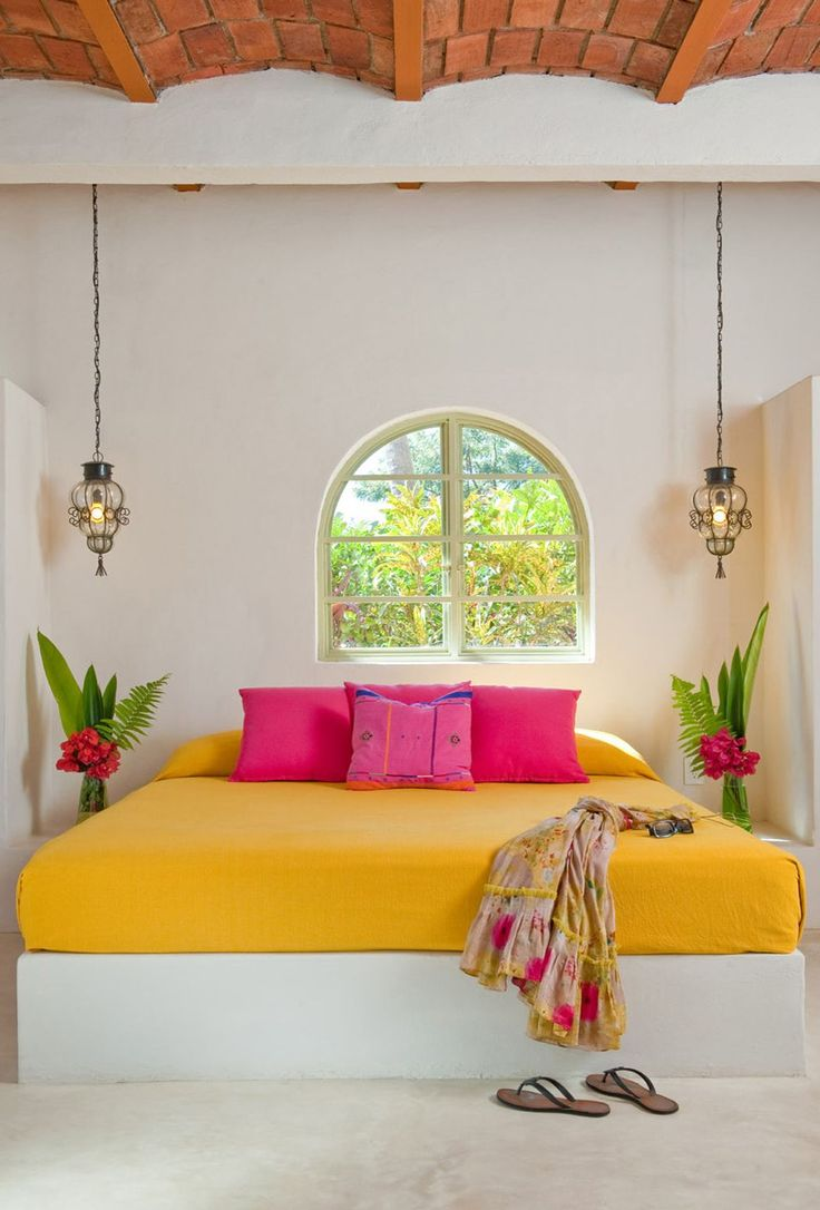 Mango colored bedding with hot pink pillows lends a tropical vibe