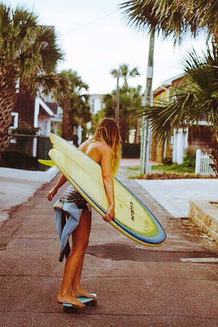 Nice young woman skating to the beach for surf all day long in the waves...