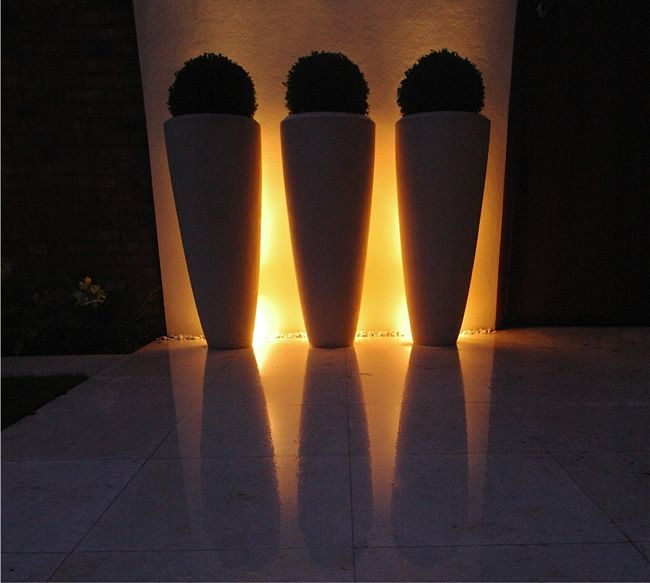 up and down lights behind the pots create an amazing glow - Contemporary Garden Design Manchester | Liverpool