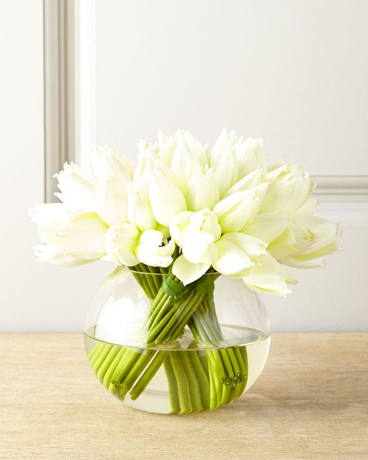 """#ONLYATNM Only Here. Only Ours. Exclusively for You. Bundles of white tulips in a round glass vace. Polyester flowers. Acrylic """"water."""" 10""""Dia. x 9""""T. Handcrafted in the USA of imported materials."""
