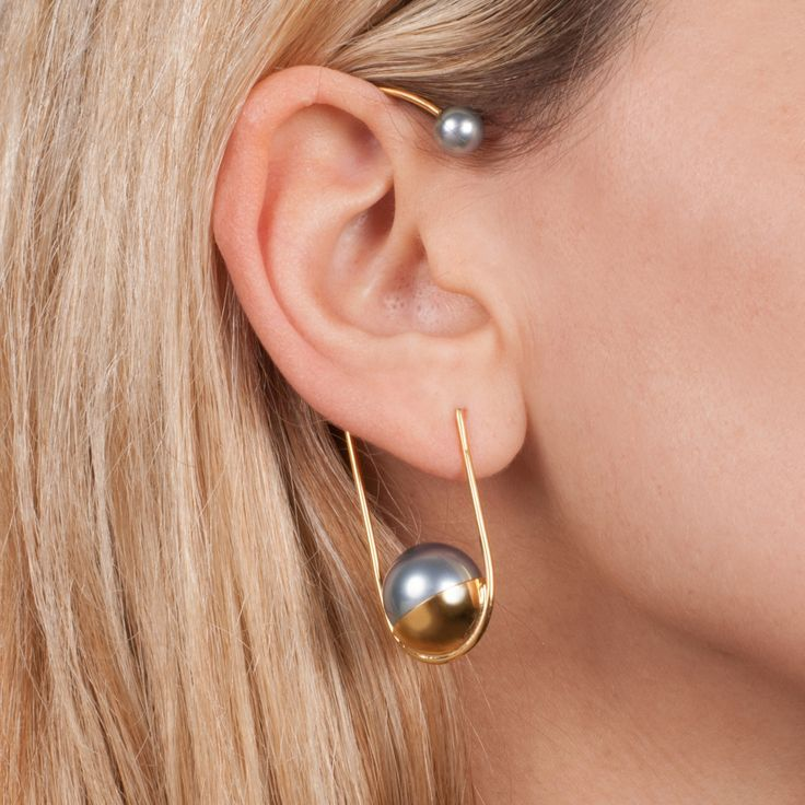 The innovative MATA earcuff is a statement piece and comes as a single earring. Inspired by a traditional 'Evil Eye' design, which acts as a protective talisman, more unconventional approach is applied with an oversized faux pearl and set in 22kt gold plated frame. This piece is made in brass, 22K yellow gold plating and accented with a grey faux pearl. Pin and butterfly are made in sterling silver.