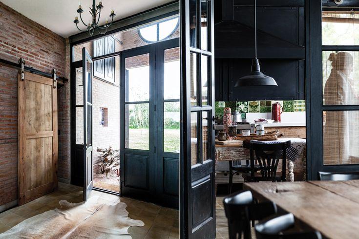 ¡Mirá la transformación de un galpón en una casa llena de diseño!  Desde el hall se accede hacia los dormitorios mediante sendas puertas colgantes en madera reciclada que corren sobre rieles y roldanas de hierro.  /Javier Csecs
