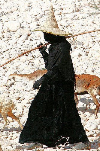 A herder in Yemen. Women in the Hadramaut area wear all black and the ones who work in the fields wear tall conical shaped straw sunhats, which contrast quite starkly with their black clothes. Everybody wants to photograph them but unfortunately women in Yemen do not like being photographed, those in Hadramaut more so.