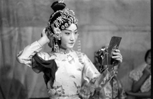 Chinese opera performer checking her hair and makeup in a mirror. Photograph by Carl Mydans. Singapore, April 1941.