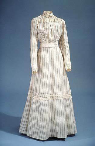 "1898-1908. Black and white print cotton in vertical floral pattern. This is a ready-made example of easily laundered dresses (they were called ""wash"" dresses), that could have been purchased at a local store or through mail-order catalogs."