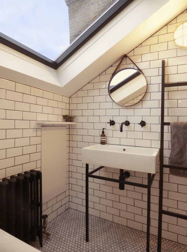 EDO Design & Construction Ltd.  Bathroom (House F) - black painted skylight - white metro tiles - bespoke basin stand - aged brass round mirror with demister - matt brass wall light
