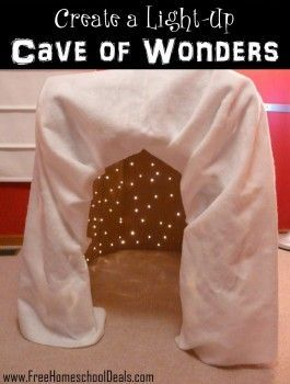 Create a light up cave of wonders.... in the playroom with ball pit! white plastic table covers, Christmas lights (blue) and purple light bulb