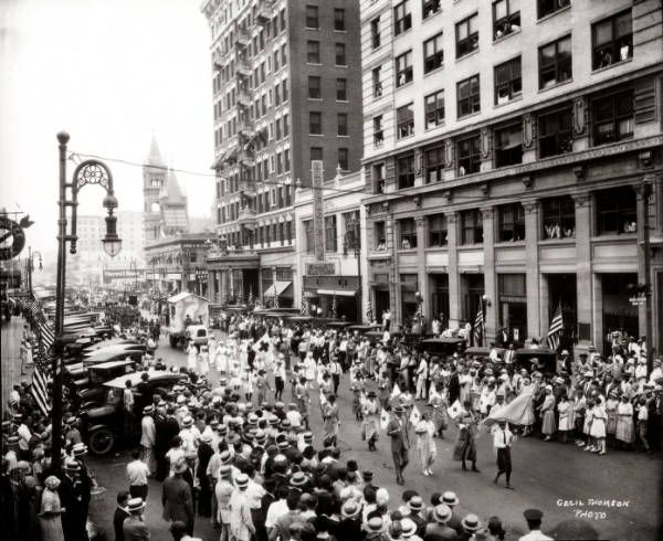 """World War I homecoming parade (Main Street at Rusk Avenue in Houston) - 1918. A view of a World War I homecoming parade, looking south on Main Street from Rusk Avenue. The parade is moving north on Main Street and is led by Red Cross representatives. Parked cars line the street as many unidentified people crowd the edge of the parade route.  George Fuermann """"Texas and Houston"""" Collection, 1836-2001 / Special Collections, University of Houston Libraries (Public Domain)."""