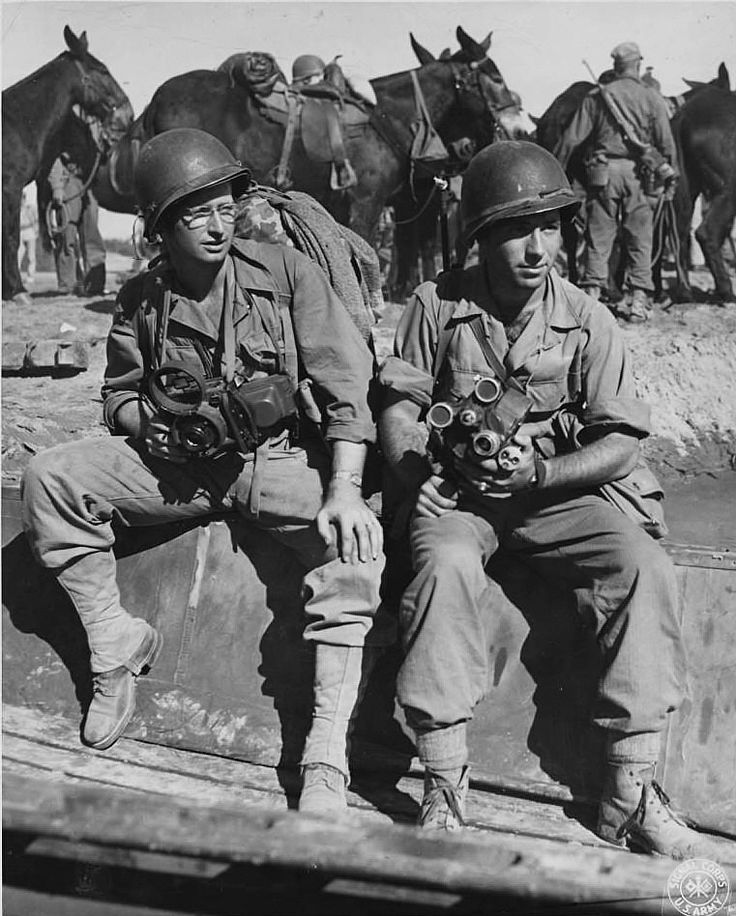 WWII Signal Corps photographers S/Sgt Yarnell of Wichita, Kansas and Sgt Pokress of NY City pack all their camera supplies in addition to regular infantry equipment as part of the combat camera pit. Photographer unknown