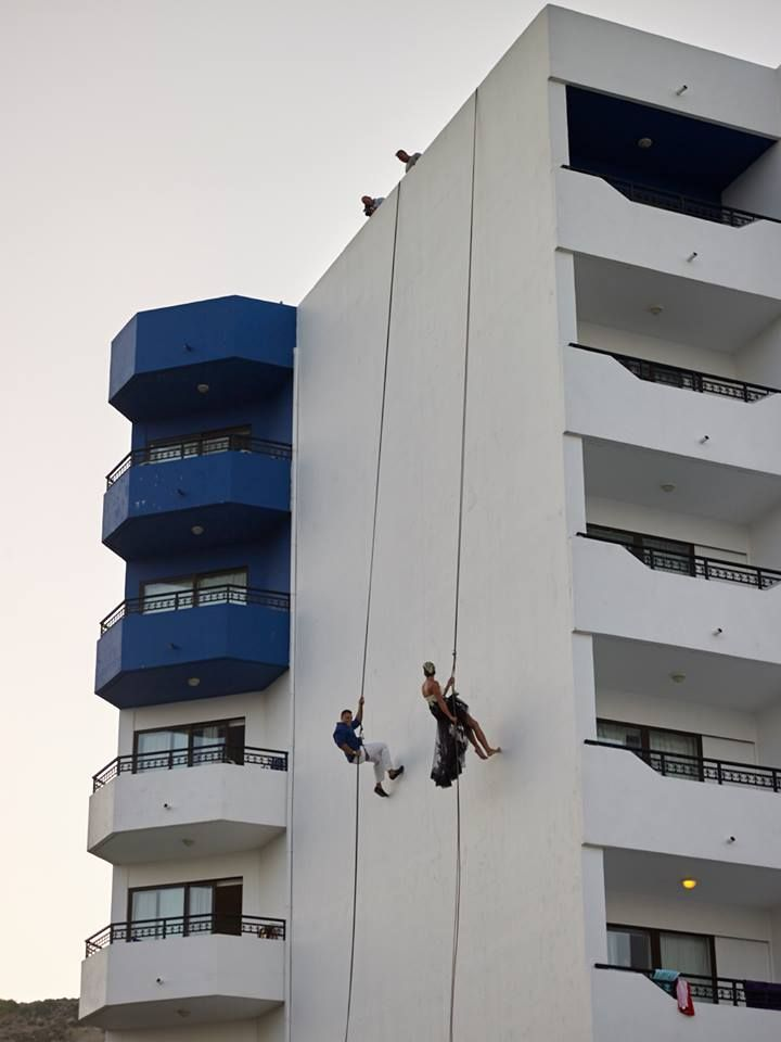 Couple of professional climbers are coming down the walls of Ammades- Epsilon Apartments to attent their wedding ceremony!