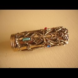 ornate lipstick case in filigreed  gold coloured metal with coloured glass stones