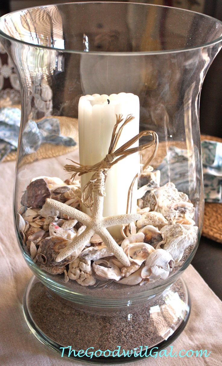 Huge glass hurricane from Goodwill filled with sand and sea shells for a centerpiece display. #nautical #coastal #centerpiece