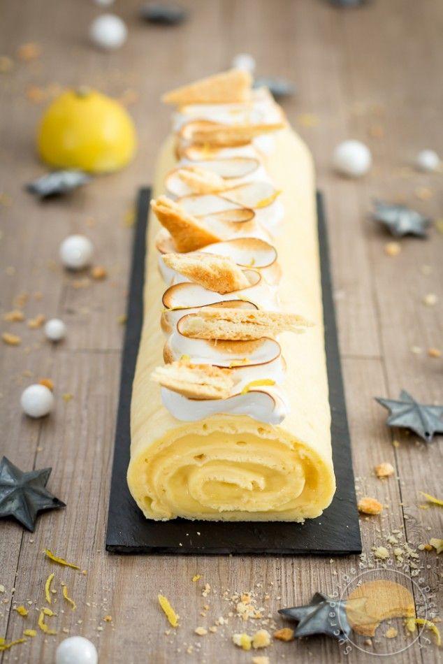 Bûche de noël roulée façon tarte au citron meringuée composée d'un biscuit soufflé à base de pâte à choux, d'une crème de citron au chocolat blanc et d'une meringue italienne parsemée de morceaux de sablé et de zestes de citron.
