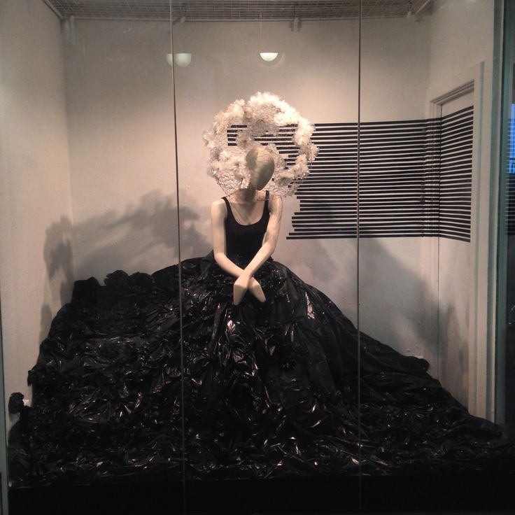 Bin bag project window installation. Dress made entirely from bin bags, bin bag flowers, wire mesh head piece and black tape