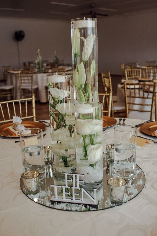 Monte Vista Venue Simple and elegant all glass centerpiece with minimal flowers of Lilliums and roses, a white laser cut table number, small gold votive with candles in and floating candles all around.