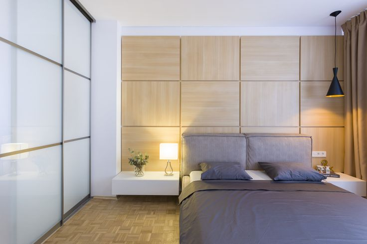 Bedroom ideas, with wood wall, modern lighting, grey bed with big pillows and a window door connecting the bedroom and the office.