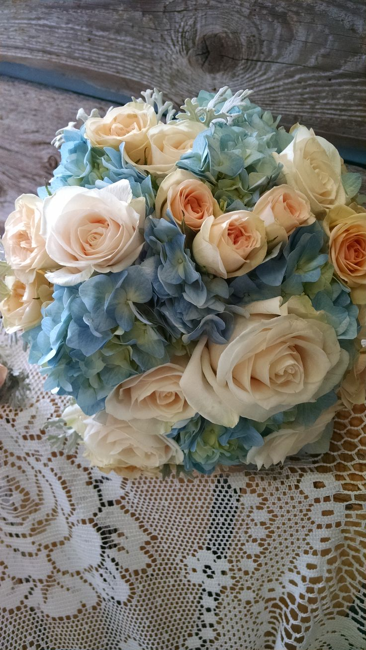 This bouquet features blue hydrangea, creme roses, and dusty miller. www.bloominggalsbouquets.com http://on.fb.me/1BT3HNz