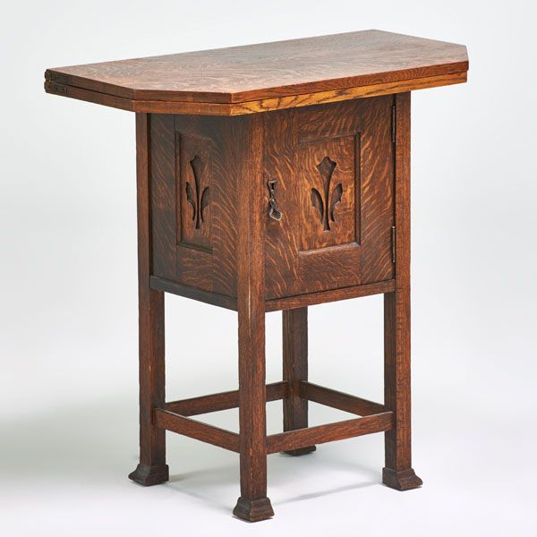 "Flip-top game table with built-in cabinet, Canada, ca. 1910; Carved quartersawn oak, patinated metal hardware; Unmarked, 30 1/2"" x 29"" x 15 5/8"" 