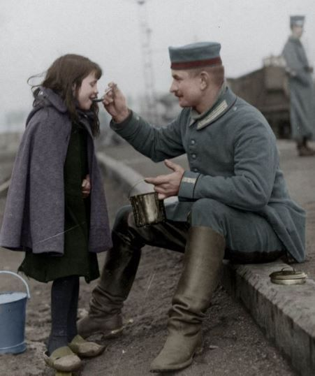 """""""German soldier shares his meal with Belgian child."""""""