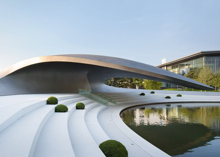 German architects HENN have created a streamlined pavilion with a curled-over steel roof for car brand Porsche at the Autostadt theme park in Wolfsburg