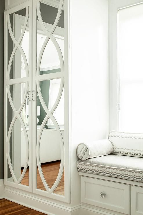 Chic bedroom boasts a built-in window seat lined with white and gray cushions placed next to a tall mirrored wardrobe cabinet finished with eclipse trim.