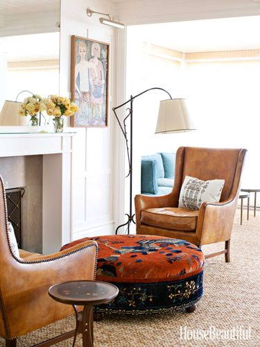 "LOVE the fab ottoman! and those wingbacks witht he antiqued leather and nailhead details! Living Room Fireplace By the living room fireplace, the seating area is like ""a cozy pub"" on chilly nights. Ole Wanscher armchairs flank an ottoman covered in antique rug fragments. Jacques Adnet lamp. Christopher Farr rug."