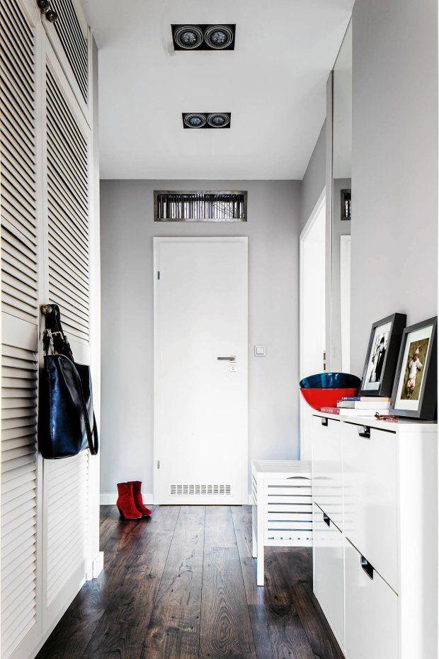PRZEDPOKOJE. Szafa sięgająca do samego sufitu ma żaluzjowe drzwi, zapewniające przepływ powietrza. Do ich ażurowej formy nawiązuje stojący naprzeciwko stołek.