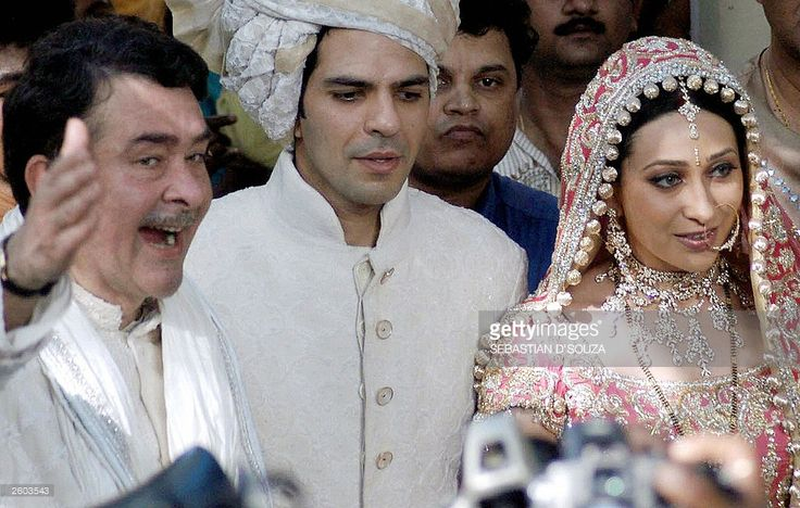 Indian film actress Karishma Kapoor (R), her new husband Sanjay Kapoor (C) and the brides father Randhir Kapoor (L) stand before a crowd of scrambling photographers (Not in the picture) in Bombay, 29 September 2003, following the couple's wedding ceremony at the Kapoor's ancestral home. The wedding of actress Karishma Kapoor to her childhood friend Sanjay Kapoor was attended by a large number of filmstars and celebrities.AFP PHOTO/Sebastian D