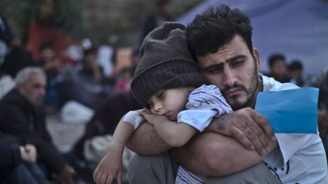 A Syrian migrant child sleeps on his father's arms on the Greek island of Lesbos. Photo: 4 October 2015