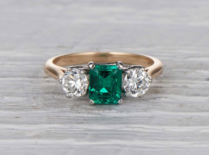 Vintage Retro Cartier engagement ring made in 18k yellow gold and platinum. Centered with an AGL certified approximately .80 carat natural Columbian emerald cut emerald accented with two transitional cut diamonds. Signed Cartier. Circa 1940