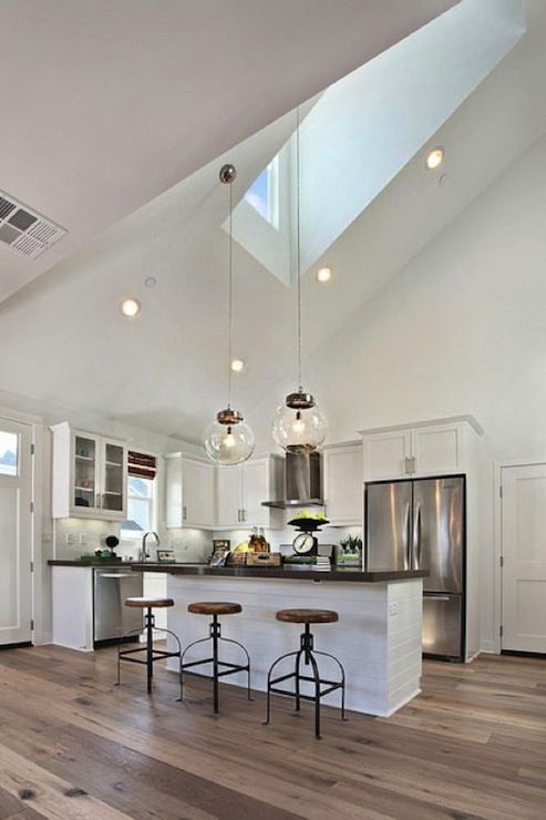 Matt White Custom Homes: L shaped kitchen design with skylight accenting white shaker cabinets paired with gray ...