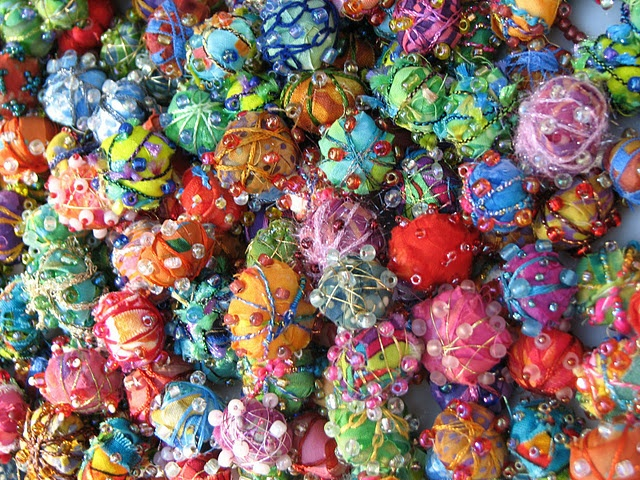 """Fabric beads    Begin by rolling your cotton ball in your hands to tightly compress it.  This added step makes for a smoother, tighter bead.  Use a long thin shred of fabric to cover the cotton ball - 1/2"""" or less w @ base, tapering to 1/4"""", about 18-20"""" long.  Dab of glue to secure the fabric.   Stitch your embellishments to the fabric."""