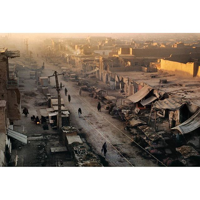 WEBSTA @ stevemccurryofficial - Street bazaar at dawn, Kandahar, 1992. The smoke from the early morning peat fires casts a haze across this Kandahar neighborhood. At this early hour the street is scattered with solitary figures. In the bottom left corner we can see three people gathered around a small fire, brewing tea. Drifting past them is a man on crutches who struggles to haul his body along while another man carries a friend on his back.